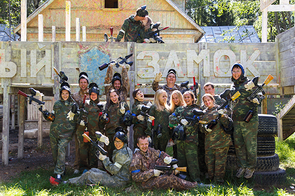 Group portrait of big happy company playing paintball